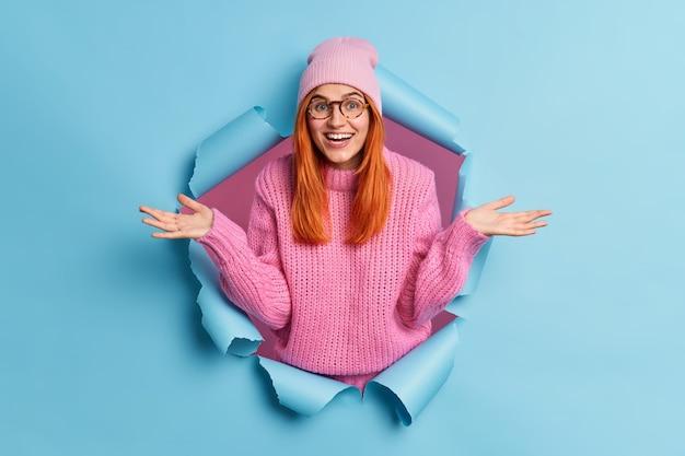 Mooie vrolijke roodharige jonge vrouw haalt schouders op en voelt zich verward als ontvangen onverwachte aanbieding een gebreide trui draagt en roze muts door papiergat breekt