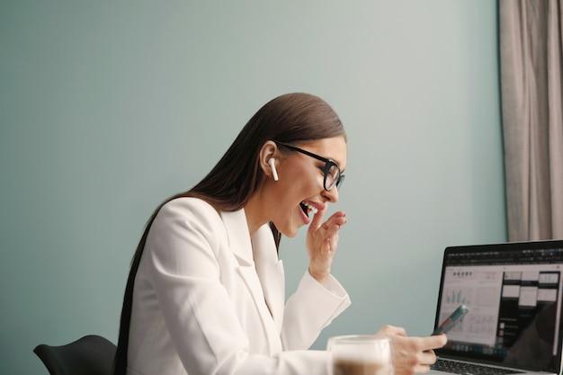 Mooie, vrolijke, schattige vrouw zit binnenshuis in kantoor met behulp van laptopcomputer en telefoon, luisterend naar muziek met oortelefoons. zakenvrouw die op laptop werkt.