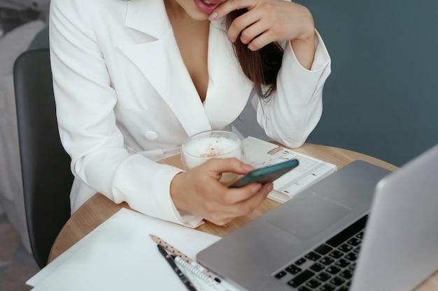 Mooie, vrolijke, schattige vrouw zit binnenshuis in kantoor met behulp van laptoptelefoon en computer met draadloze oortelefoons. zakenvrouw die op laptop werkt.