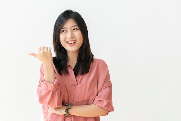 Mooie vrolijke vrouw bij een witte muur