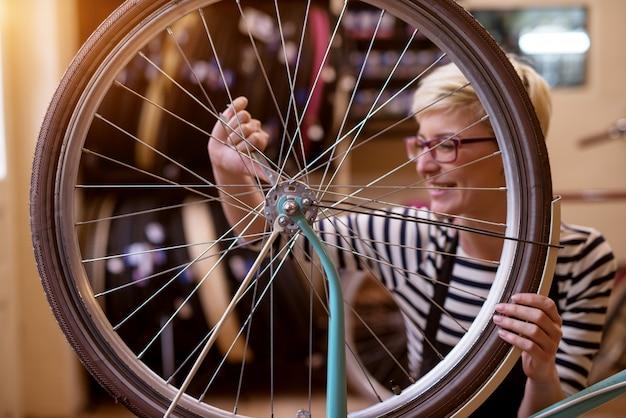 Mooie vrolijke vrouw die de schroeven van het fietswiel in de garage aanhalen.