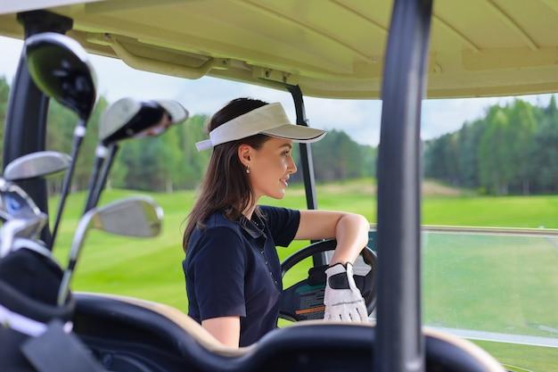 Mooie vrolijke vrouw die een golfkar drijft.