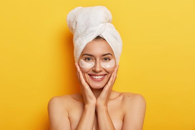 Mooie vrolijke vrouw heeft een handdoek omwikkeld om haar te drogen, houdt beide handen op de wangen, lacht zachtjes, heeft een frisse huid, geeft om de teint, draagt plekken onder de ogen