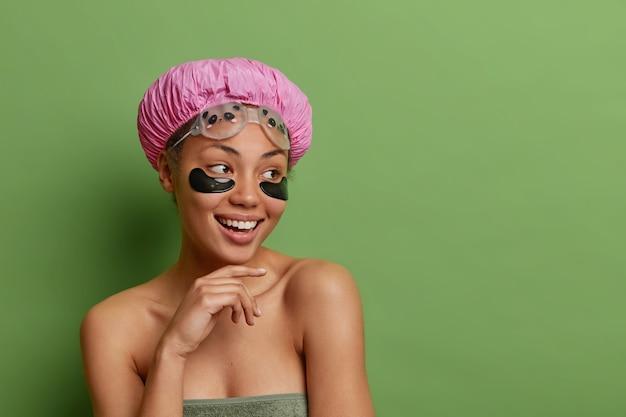 Mooie vrolijke vrouw houdt hand onder kin raakt zachtjes kaaklijn draagt waterdichte hoed badhanddoek rond naakte lichaam geïsoleerd over groene muur