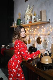 Mooie vrolijke vrouw in rode kerst pyjama kookt in de keuken, zet de ketel, interieur