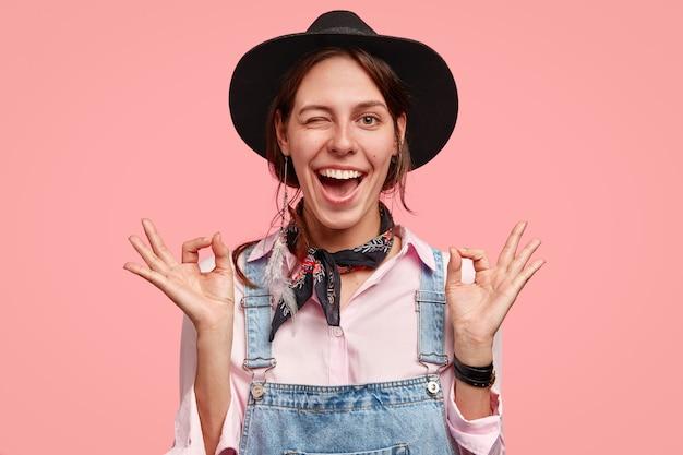 Mooie vrolijke vrouw knippert oog toont nul gebaar met beide handen, glimlacht breed, oke gebaar maakt