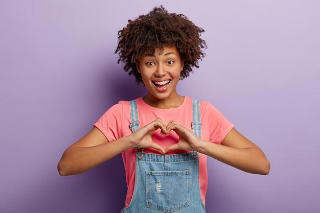 Mooie vrolijke vrouw met donkere huid, afro kapsel toont hartvorm gebaar, draagt casual t-shirt en denim overall
