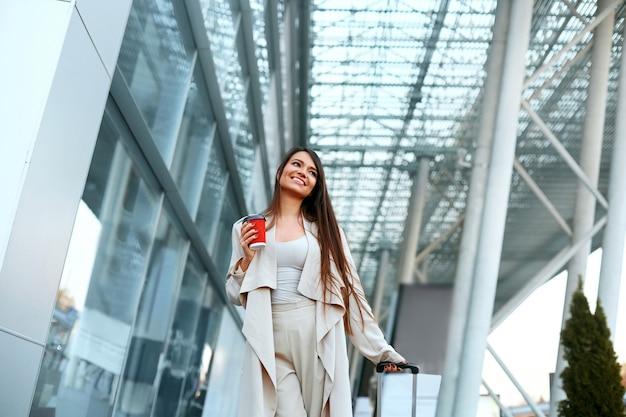 Mooie vrolijke vrouw met een koffer in de buurt van de luchthaven