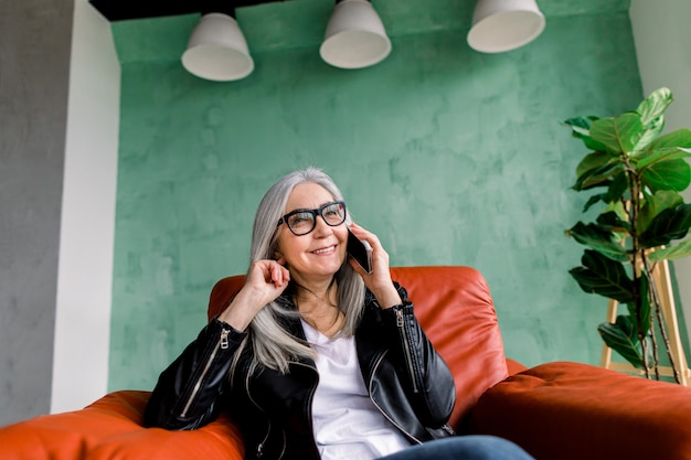 Mooie vrolijke vrouw met lang grijs haar, die telefonisch met haar vriend praat, zittend in een rode stoel in een stijlvolle zolderkamer met groene muur