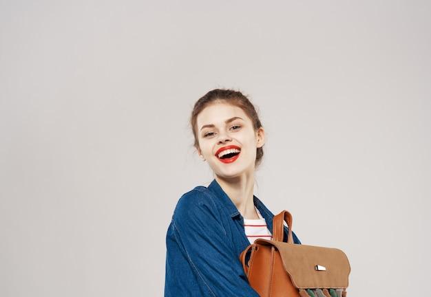 Mooie vrolijke vrouw met rugzak student opleiding kleren mode grijs