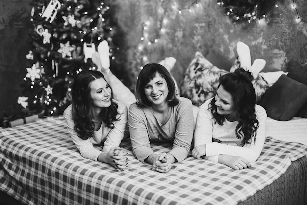 Mooie vrolijke vrouwen die gezellige pyjama's dragen die op bed liggen knuffelen