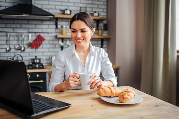 Mooie vrolijke zakenvrouw zitten aan tafel in de keuken en kijken naar laptop. ze werkt thuis. model houdt witte kop met drank en glimlach.