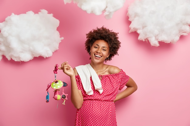 Mooie vrolijke zwangere vrouw bereidt zich voor op het moederschap, heeft een dikke buik, koopt speelgoed en kleding voor het ongeboren kind, geniet van gelukkige verwachtingen, geïsoleerd op roze muur met witte wolken erboven