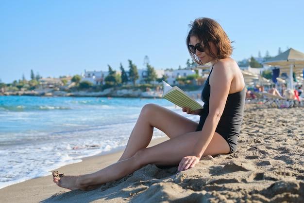 Mooie vrouw 40 jaar oud ontspannen op zandstrand, vrouwelijk leesboek
