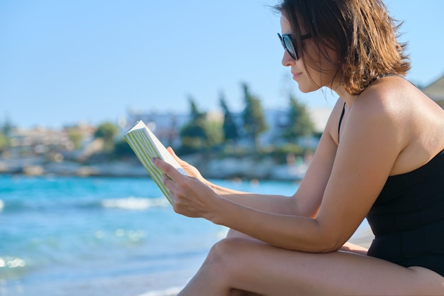 Mooie vrouw 40 jaar oud ontspannen op zandstrand, vrouwelijke leesboek, genieten van zee en zonsondergang