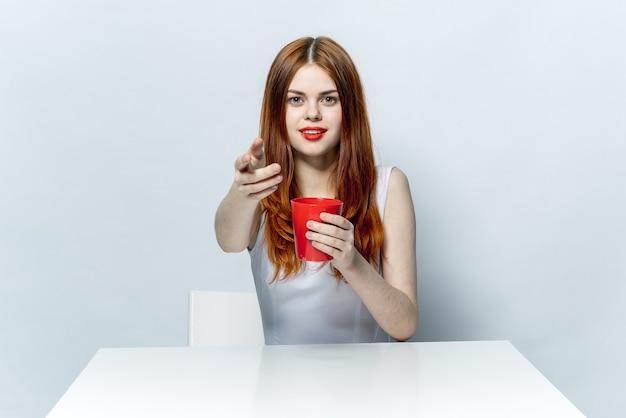 Mooie vrouw aan de tafel met rode mok in handen charme levensstijl