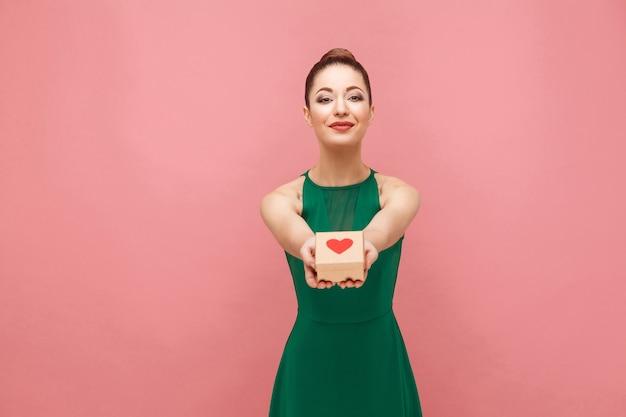 Mooie vrouw aanwezig voor u geschenkdoos met harten. expressie emotie en gevoelens concept. studio-opname, geïsoleerd op roze achtergrond