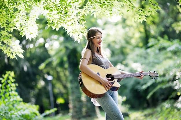 Mooie vrouw akoestische gitaar spelen in de natuur