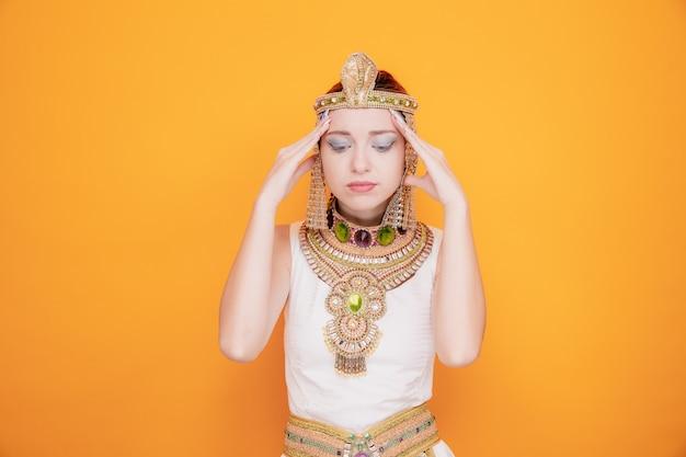 Mooie vrouw als cleopatra in oud egyptisch kostuum ziet er verward uit, hand in hand op haar slapen en probeert zich te concentreren op sinaasappel