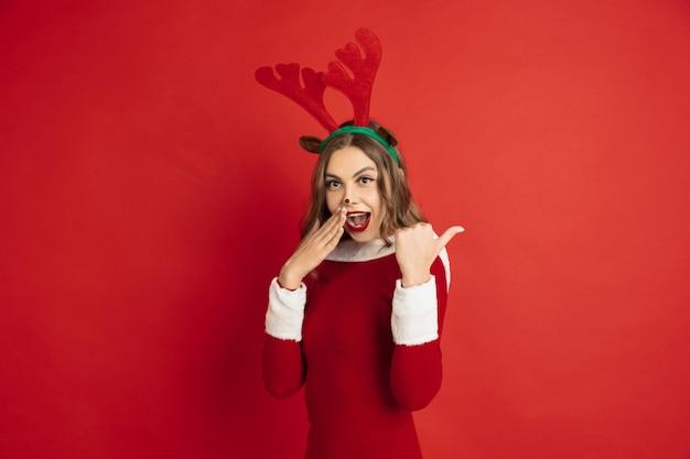 Mooie vrouw als kerst herten geïsoleerd op rood muur concept