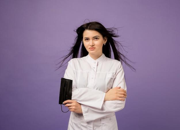 Mooie vrouw arts in een wit uniform met een zwart medisch masker staat op paars