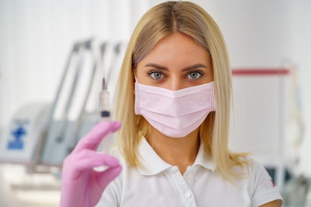 Mooie vrouw arts, verpleegster, schoonheidsspecialiste, tandarts met beschermend masker, handschoenen en spuit.
