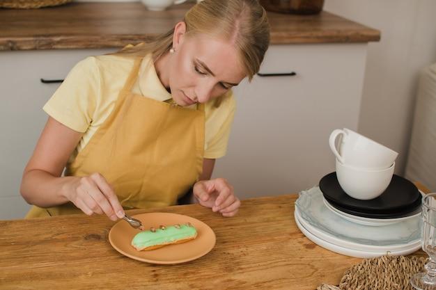 Mooie vrouw banketbakker siert de eclair. zoetwaren of kookcursussen concept