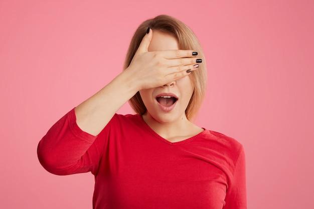 Mooie vrouw bedekt haar gezicht met de hand, doet haar mond open, probeert zich voor iemand te verbergen, gekleed in casual kleding