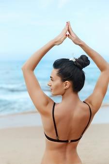 Mooie vrouw beoefent yoga en mediteert op het strand. meisje doet yoga. actieve levensstijl. gezond en yogaconcept. Premium Foto