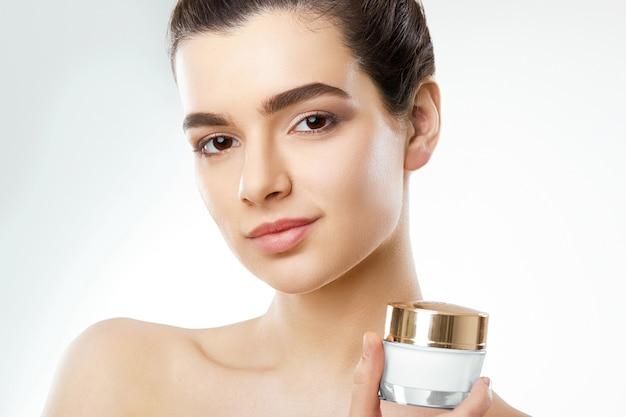 Mooie vrouw. bescherming van de huid. huidsverzorging. spa. een jonge vrouw houdt vochtinbrengende crème en lacht .. natuurlijke make-up