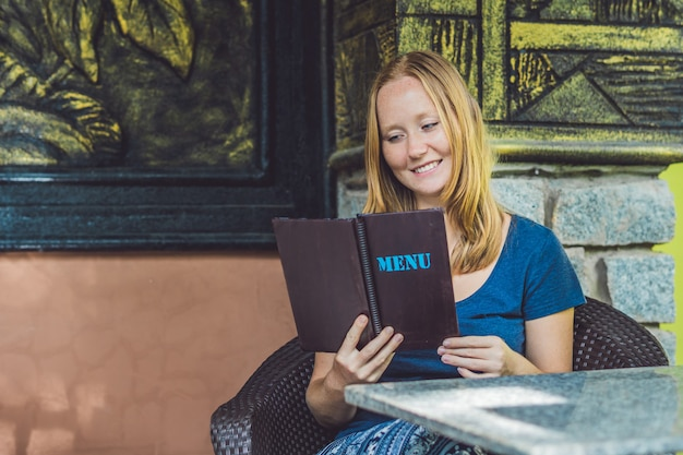 Mooie vrouw bestellen van menu in restaurant en beslissen wat te eten