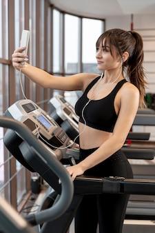 Mooie vrouw bij gymnastiek die selfies neemt