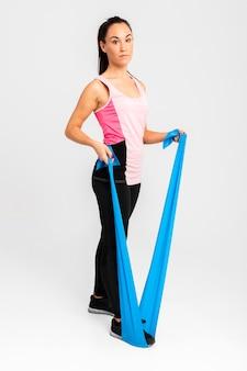Mooie vrouw bij gymnastiek het uitrekken zich wapensoefening
