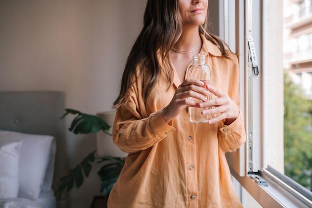 Mooie vrouw bij het raam thuis drinkwater