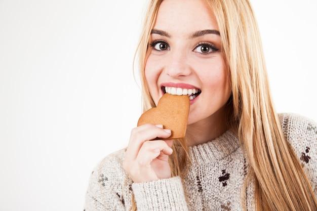 Mooie vrouw bijtend koekje