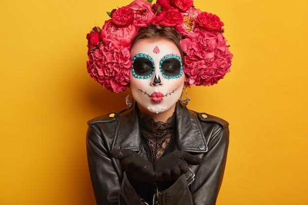 Mooie vrouw blaast mwah, houdt lippen gevouwen, draagt creatieve make-up, bereidt zich voor op carnaval, bereidt zich voor op day of dead