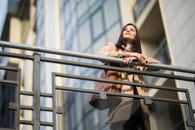 Mooie vrouw blijft op de brug op zonnige herfstdag