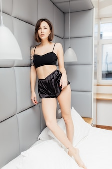 Mooie vrouw blijft op haar bed in zwarte pyjama