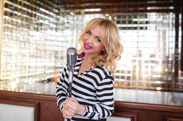 Mooie vrouw, blond, microfoon. zingen, mooie glimlach
