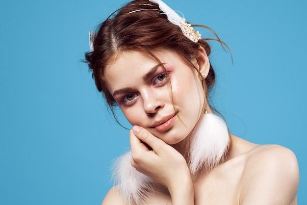 Mooie vrouw blote schouders pluizige oorbellen sieraden luxe cosmetica