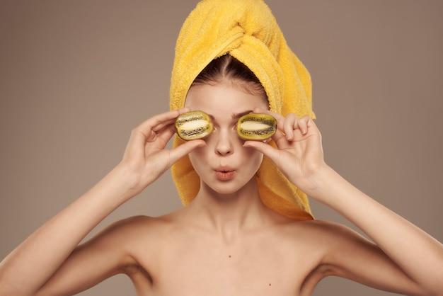 Mooie vrouw blote schouders schone huid kiwi in de hand bijgesneden weergave. hoge kwaliteit foto