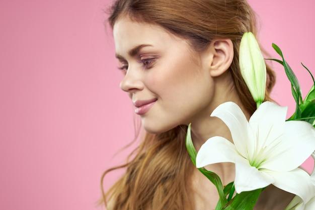 Mooie vrouw boeket bloemen charme blote schouders close-up roze achtergrond