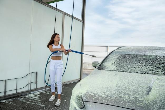 Mooie vrouw brengt schuim aan op auto vanuit een hogedrukslang