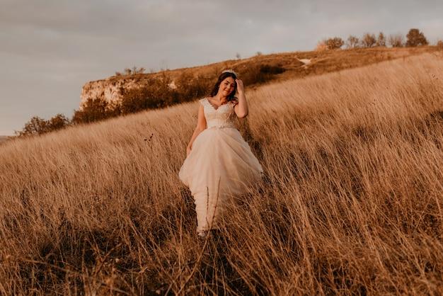 Mooie vrouw brunette bruid in witte jurk en pak lopen op hoog gras in veld in de zomer