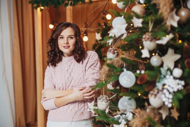 Mooie vrouw brunette in roze trui, poseren in de buurt van kerstboom