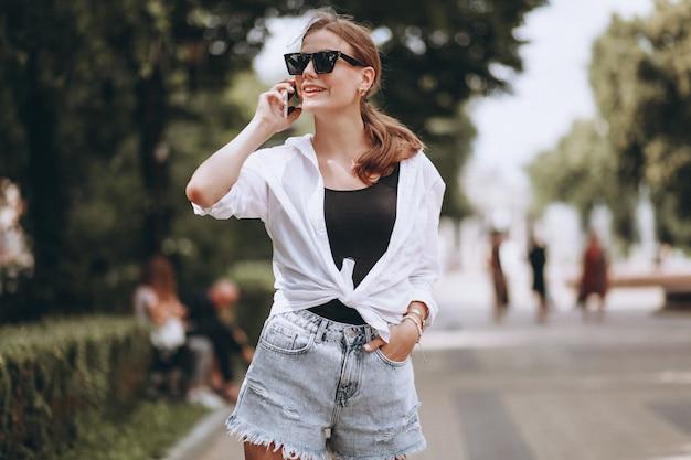 Mooie vrouw buiten de straat met behulp van de telefoon