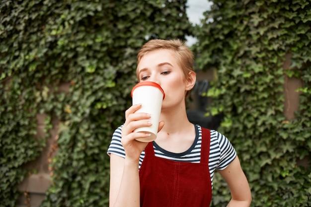 Mooie vrouw buiten een kopje koffie vrije tijd wandeling