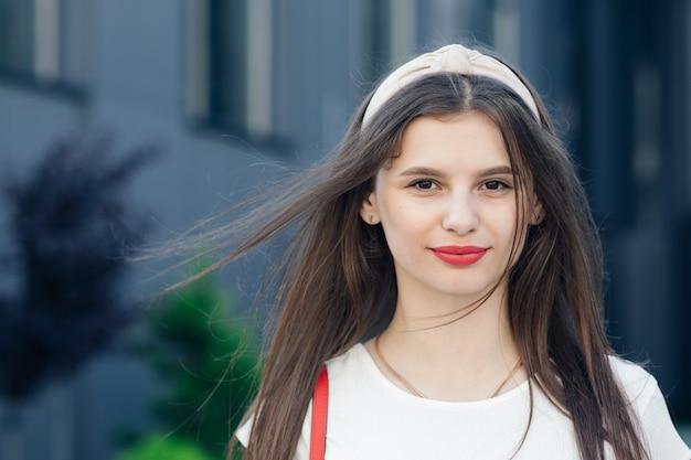 Mooie vrouw buiten. jonge lachende vrouw met plezier in de stad. rode lippenstift. portret van sexy glimlachend kaukasisch jong vrouwenmodel met glamour rode lippen, lichte make-up.