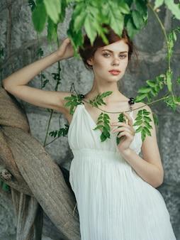 Mooie vrouw buitenshuis groene bladeren witte jurk zomerwandeling