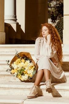 Mooie vrouw buitenshuis met boeket van lentebloemen